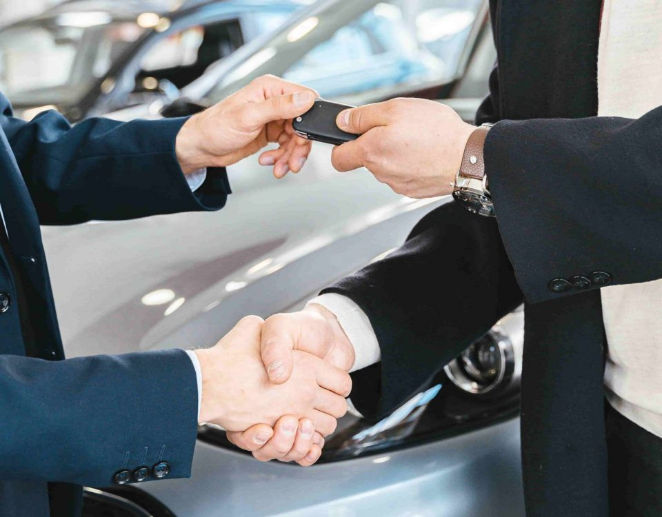 Two People Shacking Hands And One Passing Car Keys To The Other In Front Of A Vehicle